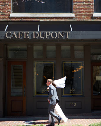 Photo of newly married couple passing Cafe DuPont on foot.