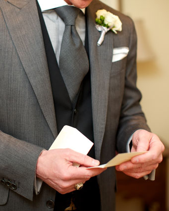 Photo of man in suit reading note
